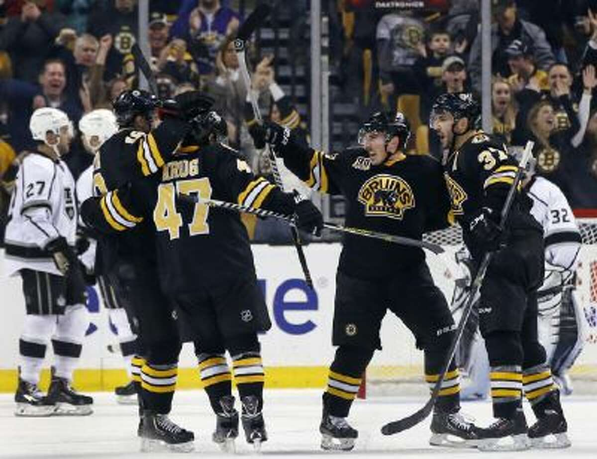 Boston Bruins left wing Brad Marchand, middle, celebrates his goal against the Los Angeles Kings with teammates including Torey Krug (47) and Patrice Bergeron (37) during the third period of an NHL hockey game in Boston Monday, Jan. 20, 2014