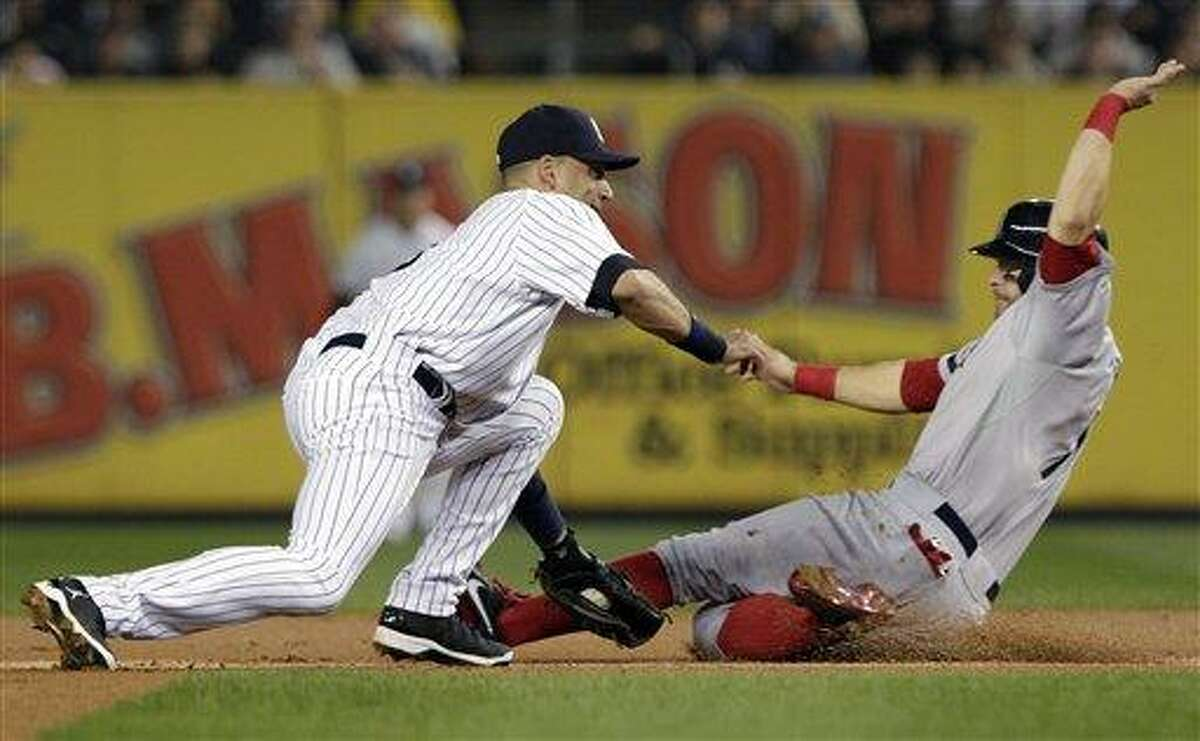 New York Yankees shortstop Derek Jeter, left, tags out Boston Red Sox's Cody Ross during the first inning of a baseball game, Wednesday, Oct. 3, 2012, in New York. (AP Photo/Frank Franklin II)