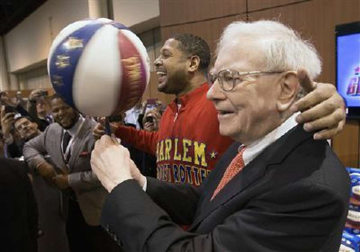 Warren Buffett, right, is watched by Detroit Lions defensive tackle Ndamukong Suh, left, as he is assisted by Harlem Globetrotter Chris ?Handles? Franklin in spinning a basketball in Omaha, Neb.