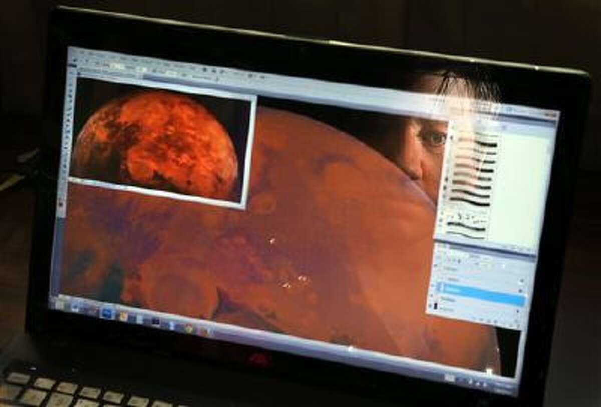 Maggie Duckworth works on a drawing of the planet Mars at her home in Bridgeton, Mo. Duckworth, 29, is among the 1,058 initial candidates chosen from a pool of 200,000 who applied for a one-way trip to Mars on the privately funded Mars One mission.