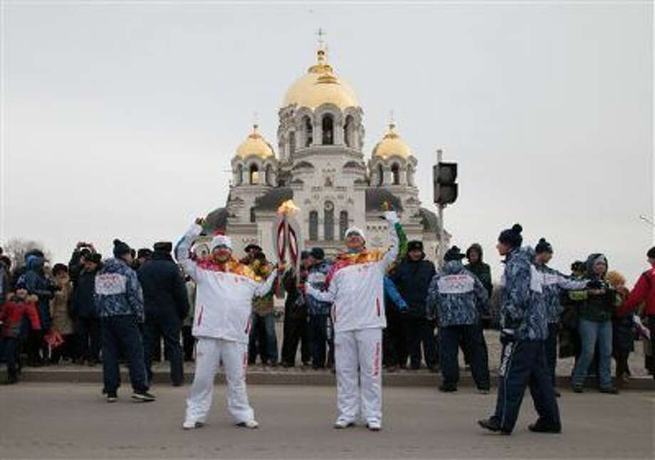 Torch bearers pose with Olympic torches during the Olympic torch relay in front of the Ascension Cathedral in Novocherkassk, about 600 miles south of Moscow, Russia. Photo: AP / Olympictorch2014.com