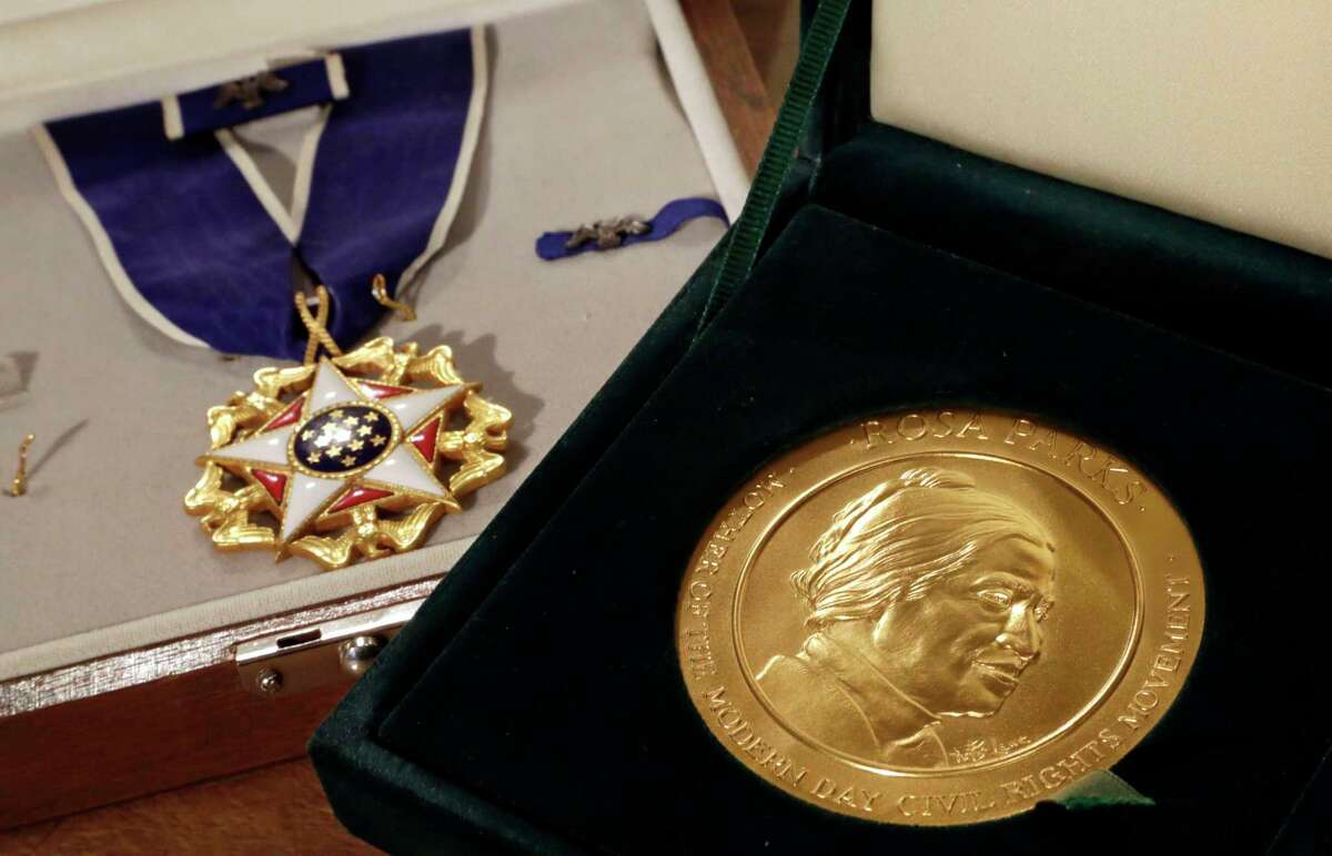 FILE - In this March 14, 2014, file photo, Rosa Parks' Presidential Medal of Freedom, left, and her Congressional Gold Medal are displayed at Guernsey's auction house, in New York. Hundreds of items that belonged to civil rights icon Rosa Parks that have been sitting unseen for years in a New York warehouse have been sold to a foundation run by the son of billionaire investment guru Warren Buffett, the younger Buffett said Thursday, Aug. 28. Howard G. Buffett told The Associated Press that his foundation plans to give the items, which include Parksí Presidential Medal of Freedom, to an institute he hasnít yet selected. (AP Photo/Richard Drew, File)
