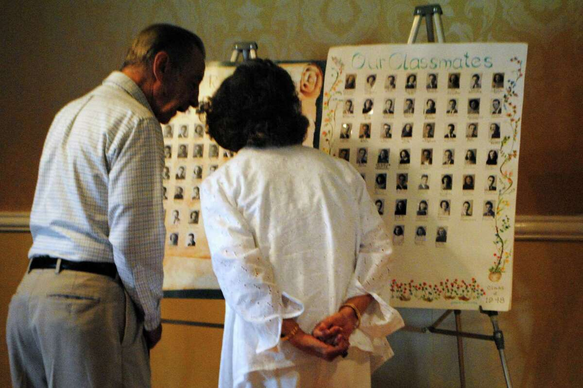 Attendees of the 1948 class reunion look at high school pictures of deceased classmates. Jessica Glenza - Register Citizen