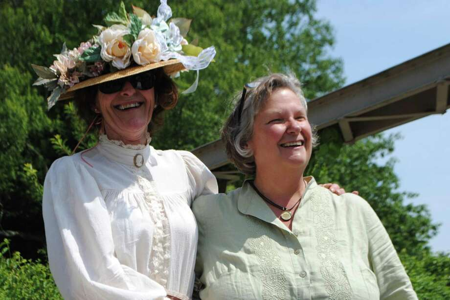 """Gerry Griswold (right) celebrates with an attendee of the centennial """"high tea"""" at Chickadee Bridge, over the Bantam River, in the White Memorial Conservation Center in Litchfield. Jessica Glenza - Register Citizen"""