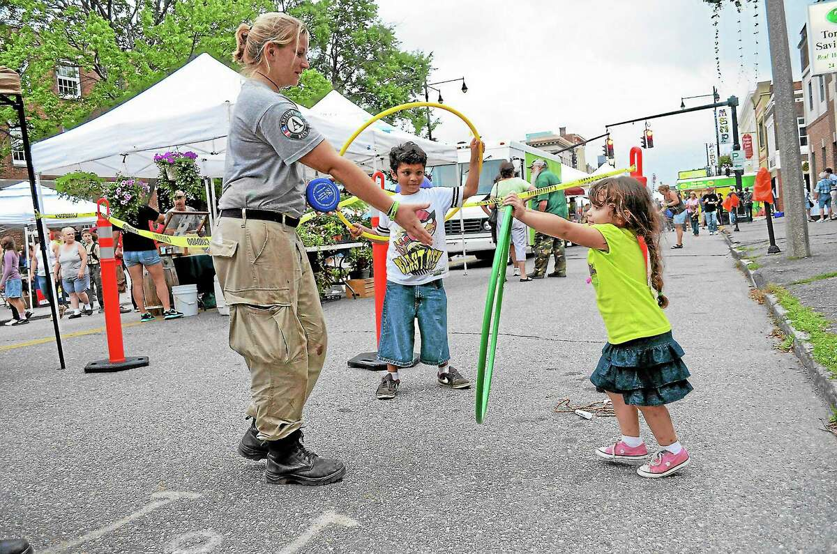 Emmy, 3, and Eric, 8, De La Cruz try out the hula hoops with Sarah Kolb of Americorps' National Civilian Community Corps during a Main Street Marketplace event in 2013.