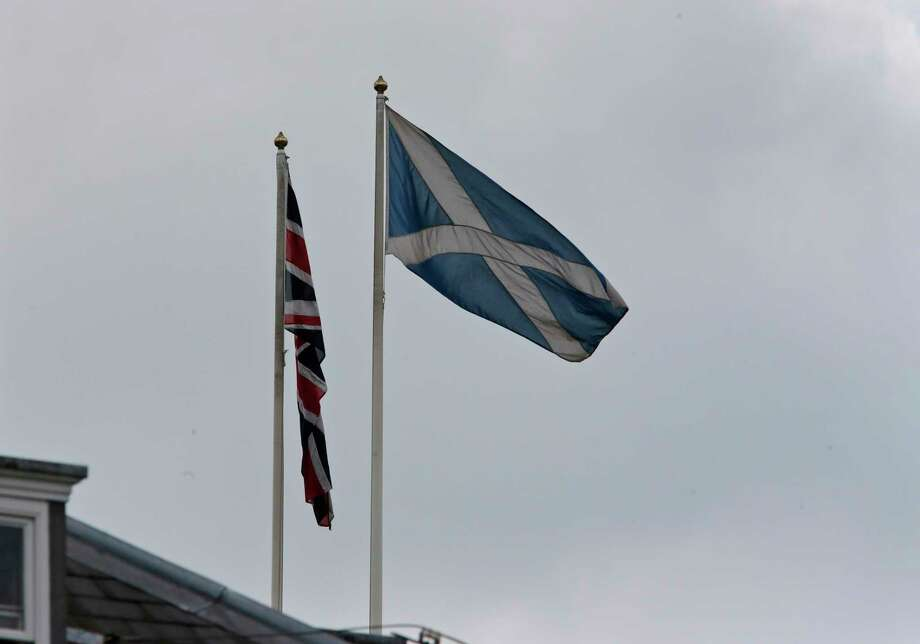 The Saltire, right, flies along with the Union Jack on a government building at Whitehall in central London, Wednesday, Sept. 10, 2014. British Prime Minister David Cameron abandoned party politics for pure emotion Wednesday, imploring Scots not to break his heart by voting to become independent from the United Kingdom. Conservative Party chief Cameron, Labour leader Ed Miliband and Liberal Democrat chief Nick Clegg all pulled out of a weekly House of Commons question session in London to make a late campaign dash to Scotland as polls suggest the two sides are neck-and-neck ahead of next week's independence referendum that could break Scotland's 307-year union with the kingdom. (AP Photo/Lefteris Pitarakis) Photo: AP / AP