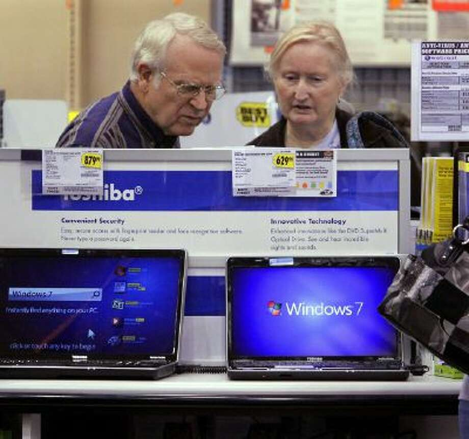 Computer shoppers read through all the options and compare prices at Best Buy in Springfield, Ill.