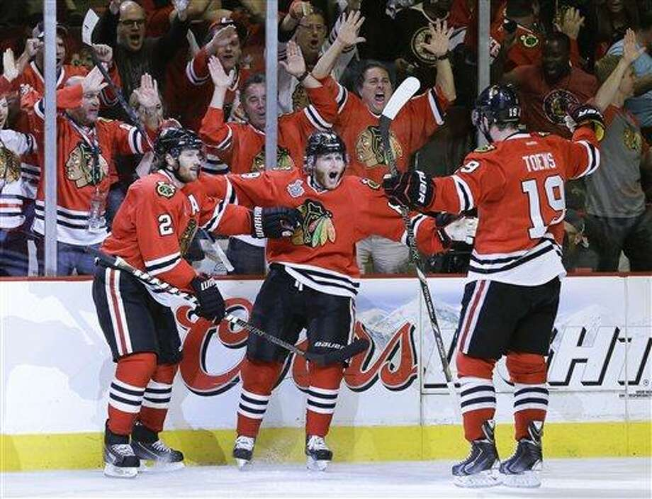 Chicago Blackhawks right wing Patrick Kane (88) celebrates with center Jonathan Toews (19) and defenseman Duncan Keith (2) after scoring a goal against the Boston Bruins in the second period during Game 5 of the NHL hockey Stanley Cup Finals, Saturday, June 22, 2013, in Chicago. (AP Photo/Nam Y. Huh) Photo: AP / AP