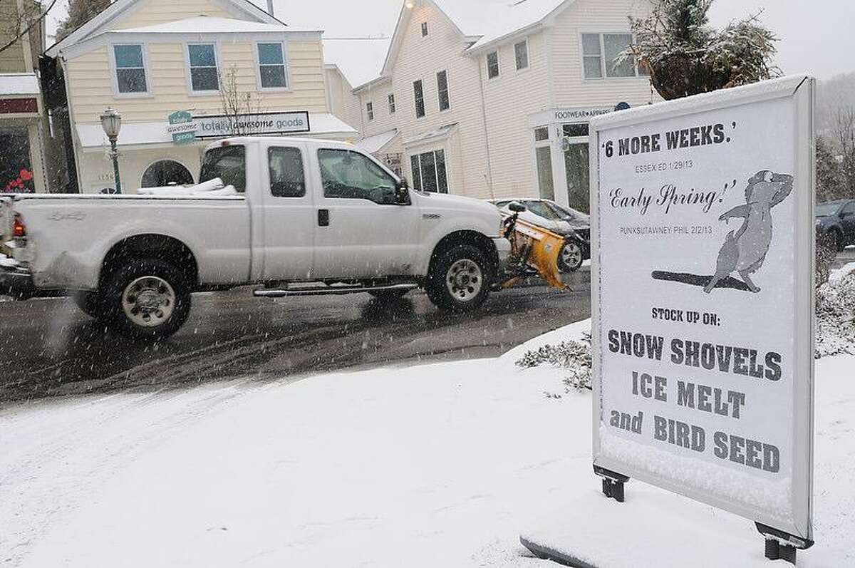 A pickup truck with a snow plow passes by a sign heralding 6 weeks to an early spring by a groundhog and advertising snow shovels ice melt and bird seed at Branford Building Supplies and Ace Hardware on Main Street in Branford, Connecticut, Friday morning February 8, 2013. Blizzard warnings have been issued for all of Connecticut, according to the National Weather Service. Connecticut residents should brace for a possible blizzard Friday and into Saturday that could dump up to two feet of snow, along with high winds and the potential for coastal flooding. Photo by Peter Hvizdak / New Haven Register