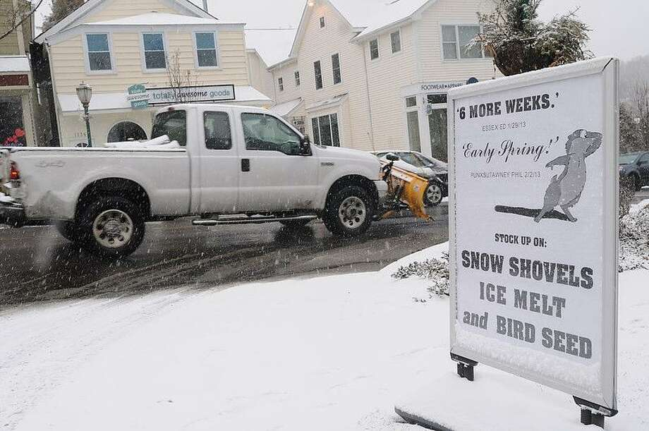 A pickup truck with a snow plow passes by a sign heralding 6 weeks to an early spring by a groundhog and advertising  snow shovels ice melt and bird seed at Branford Building Supplies and Ace Hardware on Main Street in  Branford, Connecticut, Friday morning February 8,  2013. Blizzard warnings have been issued for all of Connecticut, according to the National Weather Service. Connecticut residents should brace for a possible blizzard Friday and into Saturday that could dump up to two feet of snow, along with high winds and the potential for coastal flooding.  Photo by Peter Hvizdak / New Haven Register Photo: New Haven Register / ©Peter Hvizdak /  New Haven Register