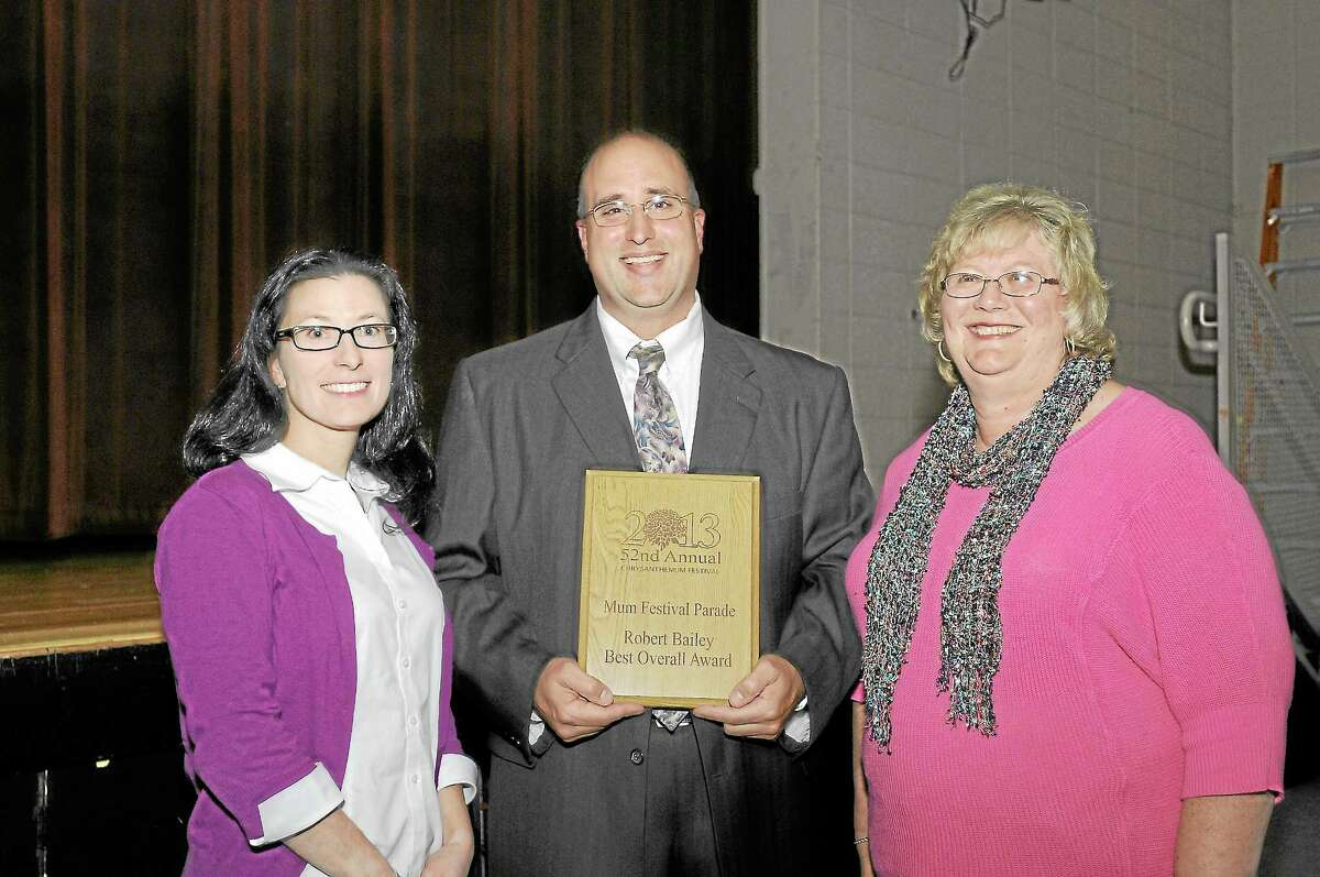 Erin King, Wayne Splettstoeszer and Beverly Bailey Foote holding a plaque won by the band at the Mum Festival.