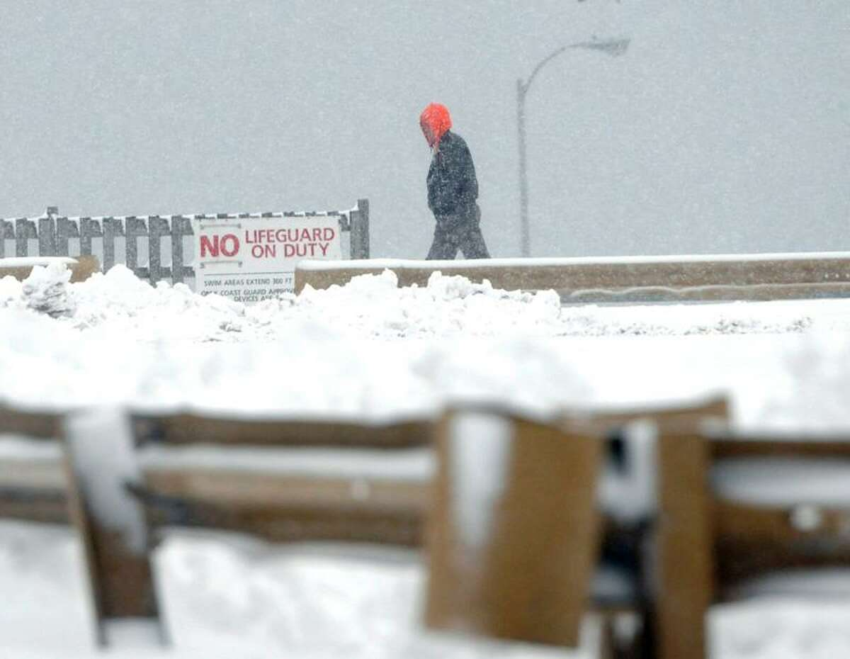 A man walks throught the snowfall on the Oak Street Deck and Beach Friday afternoon February 8, 2013 in West Haven, Connecticut. Blizzard warnings have been issued for all of Connecticut, according to the National Weather Service. Connecticut residents should brace for a possible blizzard Friday and into Saturday that could dump up to two feet of snow, along with high winds and the potential for coastal flooding. Friday, February 8, 2013. Photo by Peter Hvizdak / New Haven Register