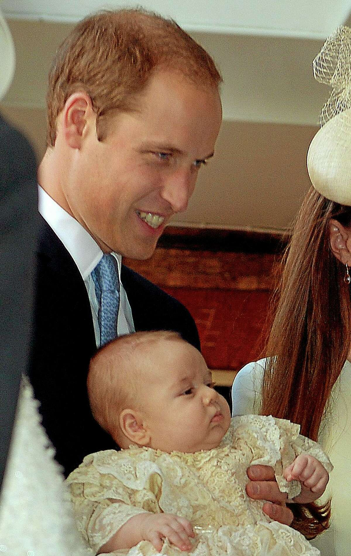 Britain's Prince William, holds his son Prince George as they arrive at the Chapel Royal in St James's Palace in London, for the christening of the three month-old Prince Wednesday Oct. 23, 2013. The 3-month-old future monarch, Prince George will be christened Wednesday with water from the River Jordan at a rare four-generation gathering of the royal family in London. (AP Photo/John Stillwell/Pool)