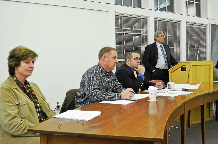 From left, selectmen Nancy Schnyer and Jon Truskauskas, First Selectman Mike Criss, and moderator Andrew Kasznay listen to resident questions during a Harwinton town meeting Tuesday. Photo: Kate Hartman—Register Citizen