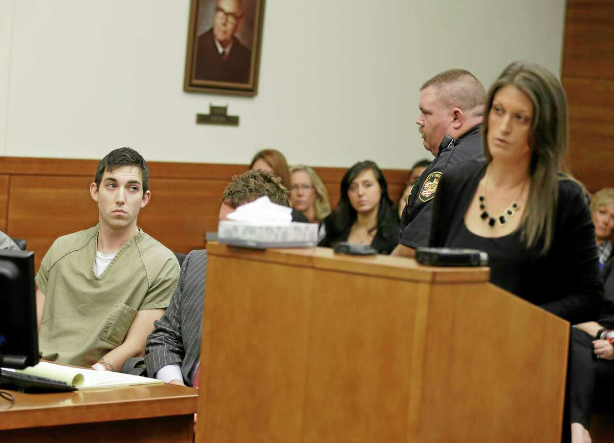 Matthew Cordle, left, looks at Angela Canzani, the victims daughter, as she reads a statement during Cordle's sentencing Wednesday, Oct. 23, 2013, in Columbus, Ohio. Cordle was sentenced to 6 1/2 years in prison for causing a fatal wrong-way crash after a night of heavy drinking, which Cordle confessed to in an online video. Cordle had faced up to 8½ years for killing Vincent Canzani in a June 22 crash. He had been on his way home after a night of drinking at bars near downtown Columbus. (AP Photo/Tony Dejak)