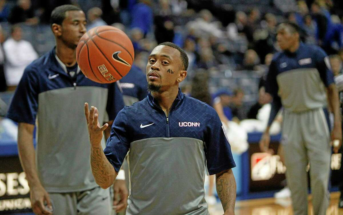 """UConn guard Ryan Boatright warms up for Thursday's game against Memphis. Boatright wrote the initials """"AW"""" on his cheek to honor his cousin who was shot to death in Aurora, Ill."""