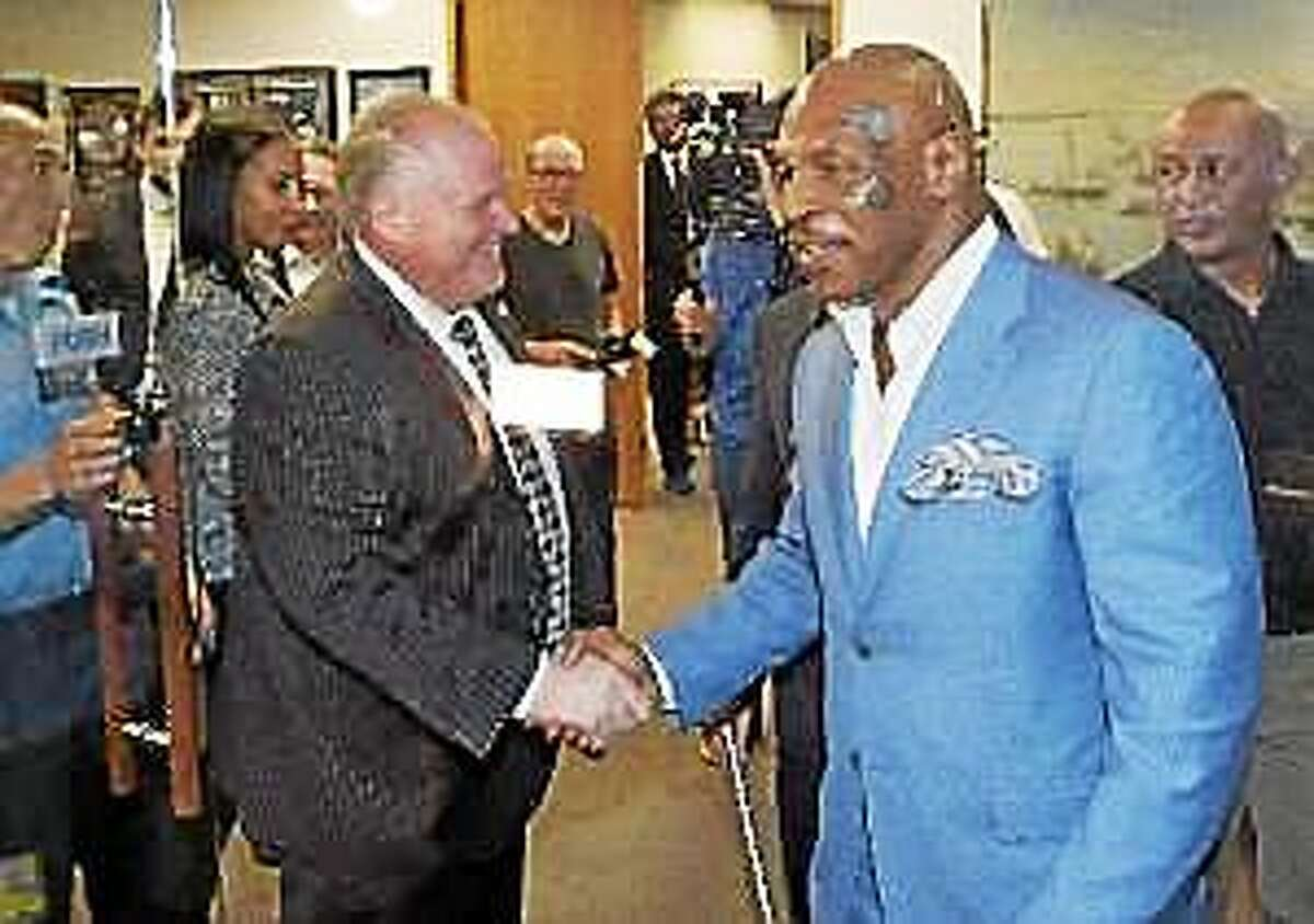 Toronto Mayor Rob Ford, center, shakes hands with former heavyweight boxing champion Mike Tyson at City Hall in Toronto on Tuesday, Sept. 9, 2014.