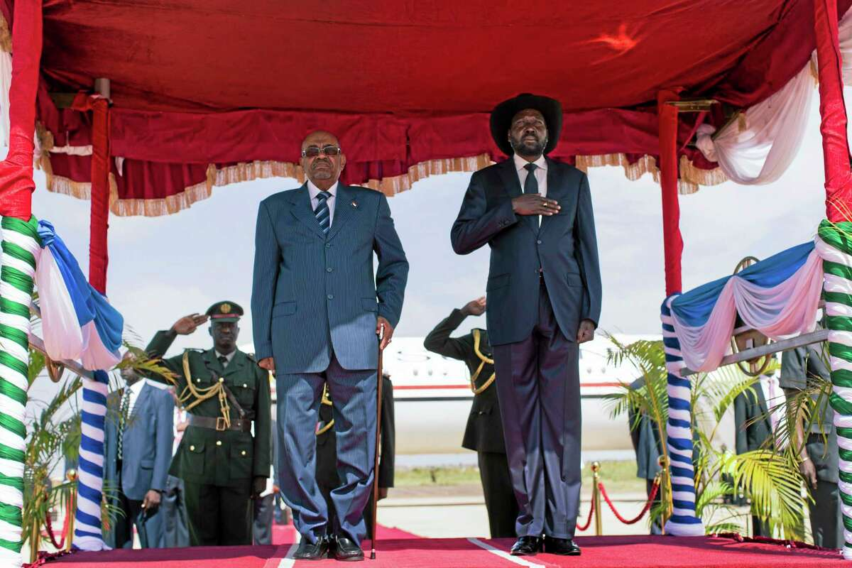 Sudan's President Omar al-Bashir, left, and South Sudan's President Salva Kiir, right, stand for the playing of national anthems on al-Bashir's arrival at the airport in Juba, South Sudan Tuesday, Oct. 22, 2013. The two leaders met Tuesday to discuss a range of issues including the situation in Abyei. (AP Photo/Mackenzie Knowles-Coursin)