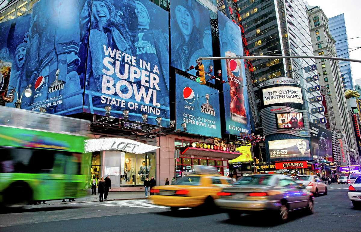 "Large signs advertising the Super Bowl are seen on 42nd Street by Times Square on Monday in New York. Preparations for fan venues and activities for the upcoming Super Bowl are starting to appear along several blocks of Broadway, part of which has been dubbed ""Super Bowl Boulevard."""