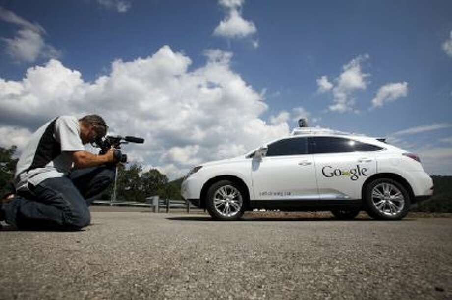This Sept. 3, 2013 photo shows a videographer photographing the Google self-driving car during a news conference at the Virginia Tech Transportation Institute's Smart Road in Blacksburg Va.