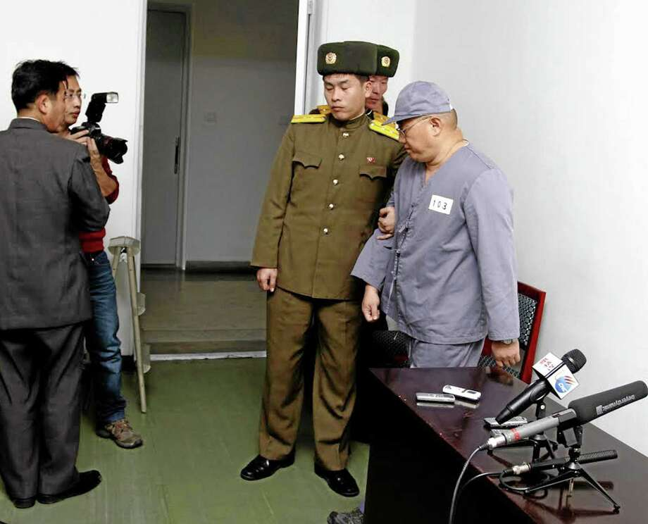 American missionary Kenneth Bae, right, leaves after speaking to reporters at Pyongyang Friendship Hospital in Pyongyang Monday, Jan. 20, 2014. Bae, 45, who has been jailed in North Korea for more than a year, appealed for the U.S. to do its best to secure his release. (AP Photo/Kim Kwang Hyon) Photo: AP / AP