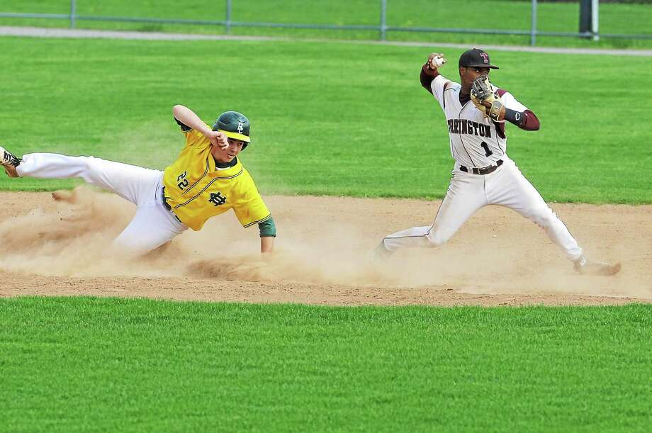 Torringtonís Stanly Rijo throws to first base as Holy Crossí Ben Brown slides into second base. Holy Cross won 7-1. Photo: Laurie Gaboardi — Register Citizen