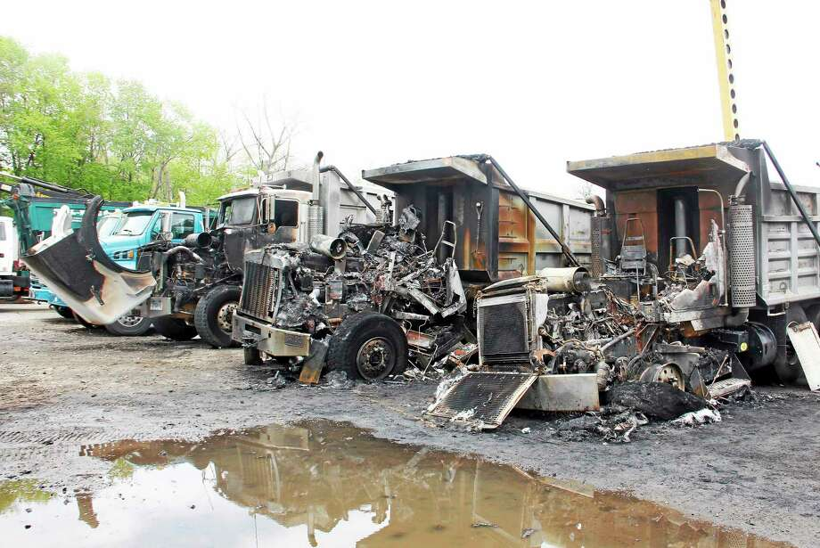 Three trucks destroyed by an early-morning blaze parked on a lot at Mountain Top Trucking Tuesday in Torrington. The trucks were a total loss, with the damage estimated at $200,000. Photo: Esteban L. Hernandez — Register Citizen