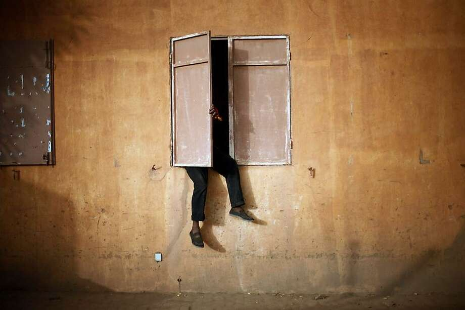 A Malian man sits on a window sill to watch the Nigeria versus Mali Africa Cup of Nations semifinal soccer match taking place in South Africa, in Gao, northern Mali, Wednesday, Feb. 6, 2013. (AP Photo/Jerome Delay) Photo: ASSOCIATED PRESS / AP2013