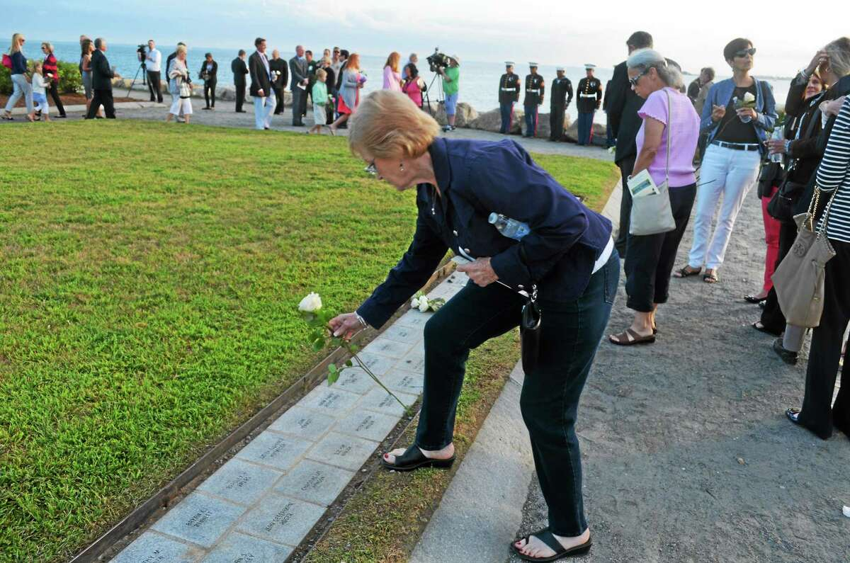 A family member of one of the victims of the 9/11 terrorist attacks places a flower at the state's memorial Wednesday in Westport.
