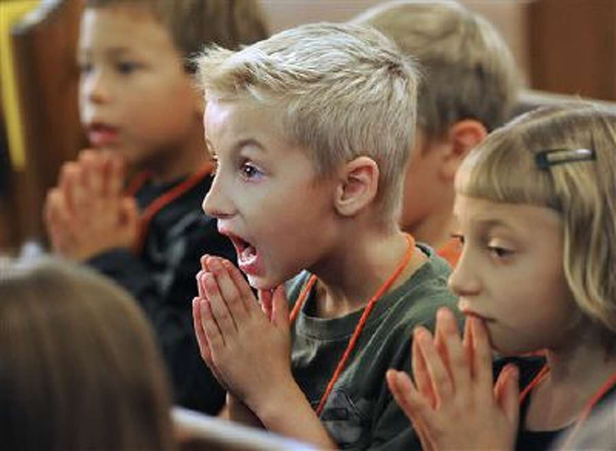 Marcus Robinson prays alongside other kids during a bible camp Oct. 8 at a church in Shirley, Ind. Many public schools still grapple with the issue of separation between church and state and won't allow such religious practices. (AP Photo/Daily Reporter, Tom Russo)