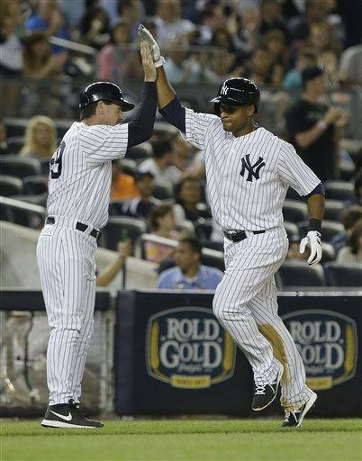 New York Yankees' Zoilo Almonte, right, celebrates with third base coach Rob Thomson as he heads to home plate after hitting a home run during the sixth inning of a baseball game on Friday, June 21, 2013, in New York. (AP Photo/Frank Franklin II)