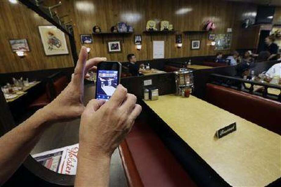 """Liz O'Neil, of Montclair, N.J., takes a photograph of a reserved booth where the last show of the HBO series """"The Sopranos"""" was filmed at Holsten's ice cream parlor, Wednesday, June 19, 2013, in Bloomfield, N.J. The sign was put on the booth where the last scene was filmed in honor of actor James Gandolfini who died Wednesday in Italy. He was 51. (AP Photo/Julio Cortez) Photo: AP / AP"""
