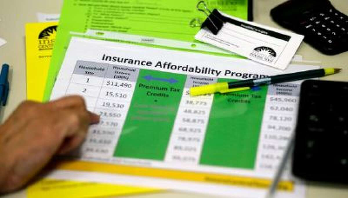 In this Oct. 1, 2013 photo, a volunteer counselor with Insure Central Texas uses a chart to help explain health insurance options in Austin, Texas.