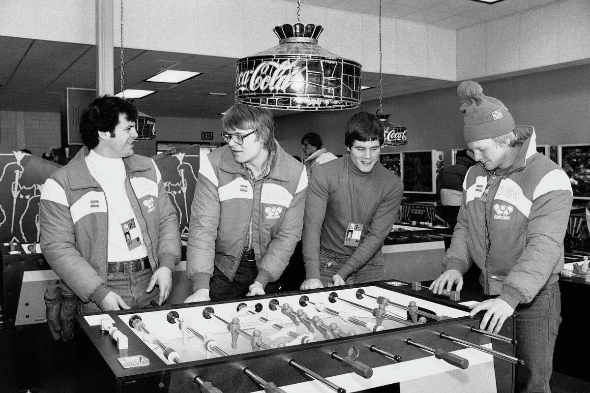 In this Feb. 10, 1980 file photo, U.S. Olympic hockey players, from left, Michael Eruzione, Phil Verchota, John Harrington and Bob Suter play foosball in the game room of the Olympic village in Lake Placid, N.Y.