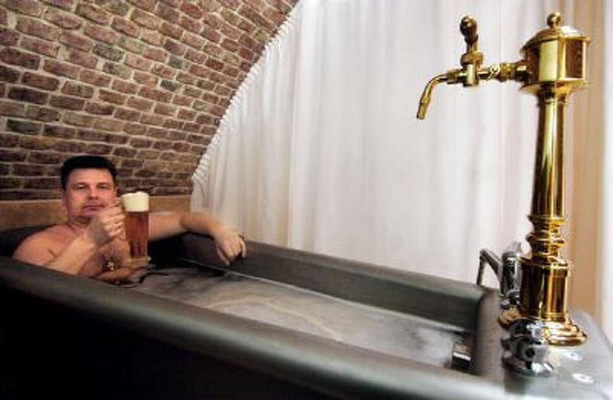 Grasping a large beer, Russian businessman Andrei relaxes in Chodova Plana near Mariendbad in a herbal beer bath, the latest Czech