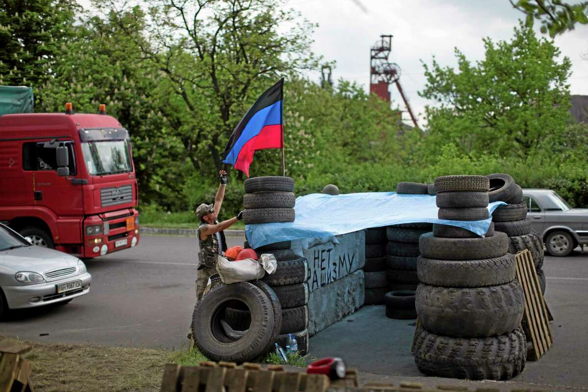 Pro-Russian insurgents with the self-proclaimed Donetsk People's Republic man a checkpoint by the Karl Marx coal mine seen in the background near Korsun, a small town about 30 km north-east from Donetsk, eastern Ukraine, Tuesday, May 13, 2014. The words on the wall of barricades read