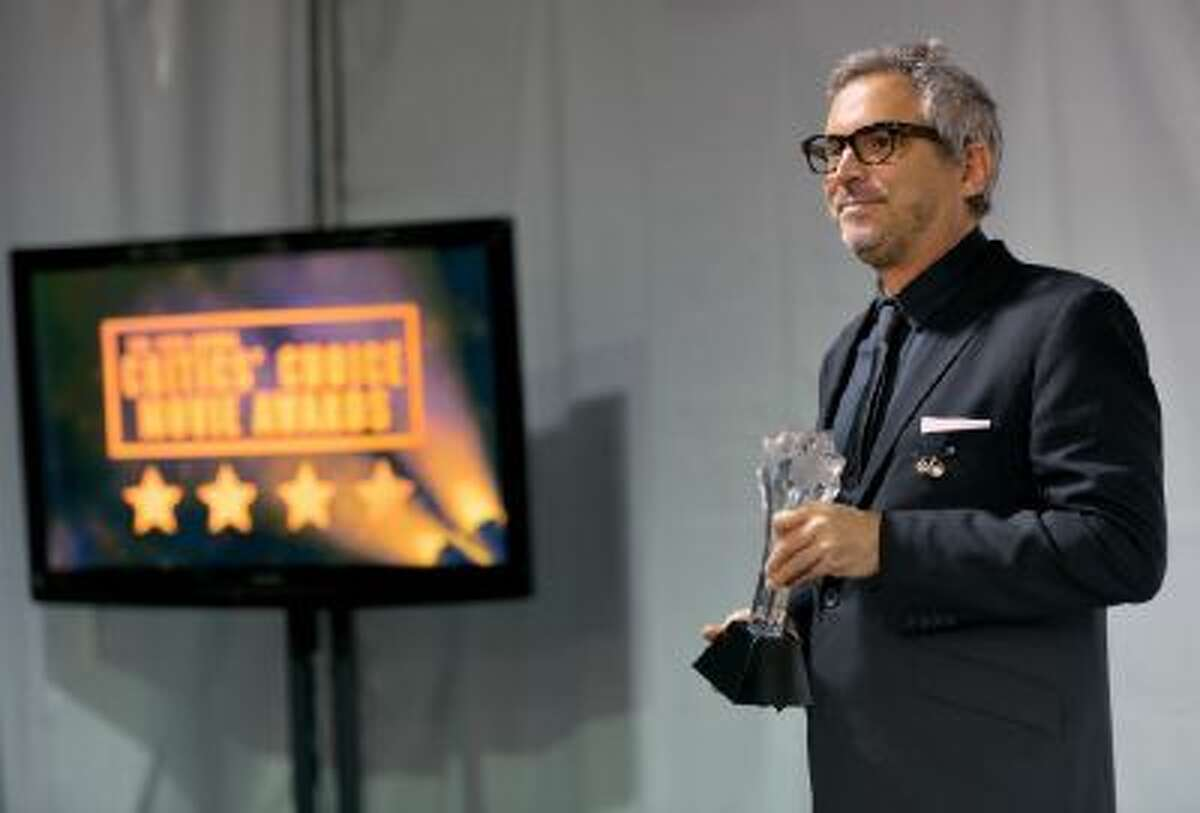 Alfonso Cuaron poses with the award for best director for