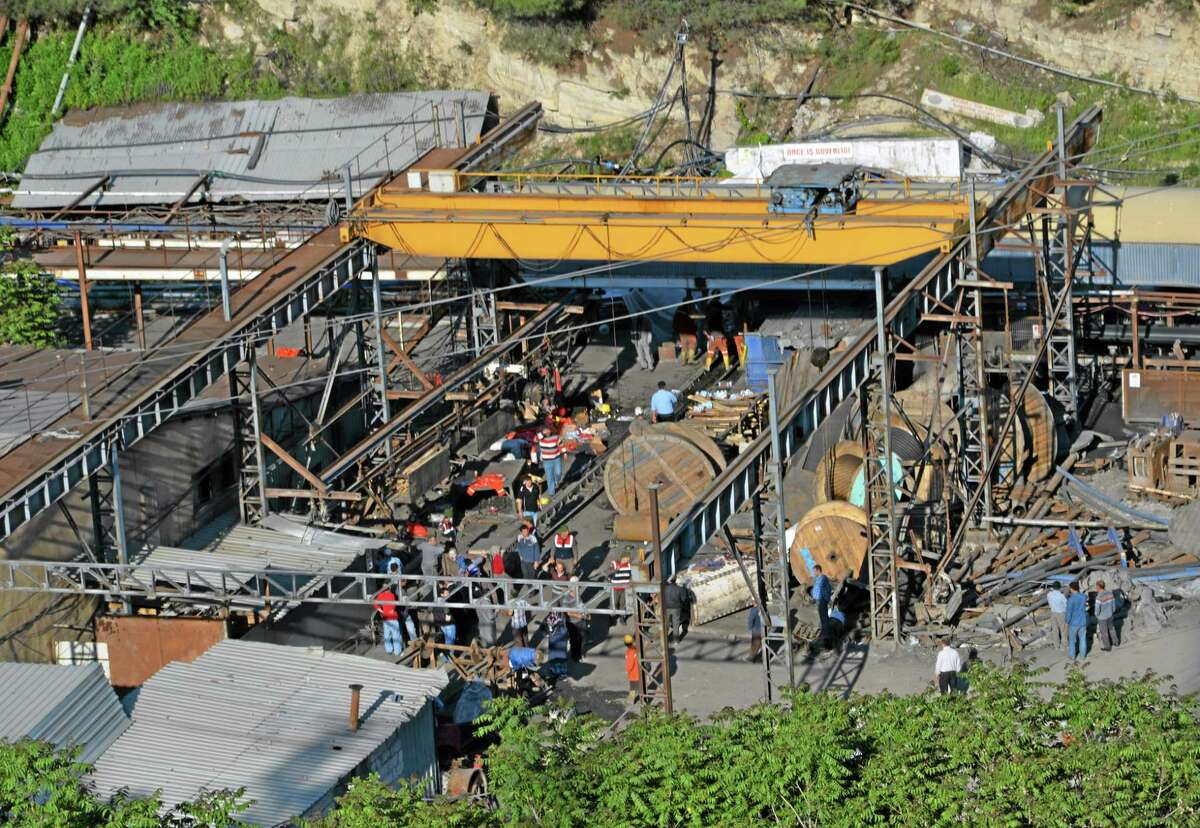 Rescue workers at the entrance of the mine after an explosion and fire at a coal mine in Soma, in western Turkey, Tuesday, May 13, 2014. An explosion and fire at a coal mine in western Turkey killed at least one miner Tuesday and left up to 300 workers trapped underground, a Turkish official said. Twenty people were rescued from the mine in the town of Soma in Manisa province but one later died in the hospital, Soma administrator Mehmet Bahattin Atci told reporters. The town is 250 kilometers (155 miles) south of Istanbul. (AP Photo/IHA) TURKEY OUT