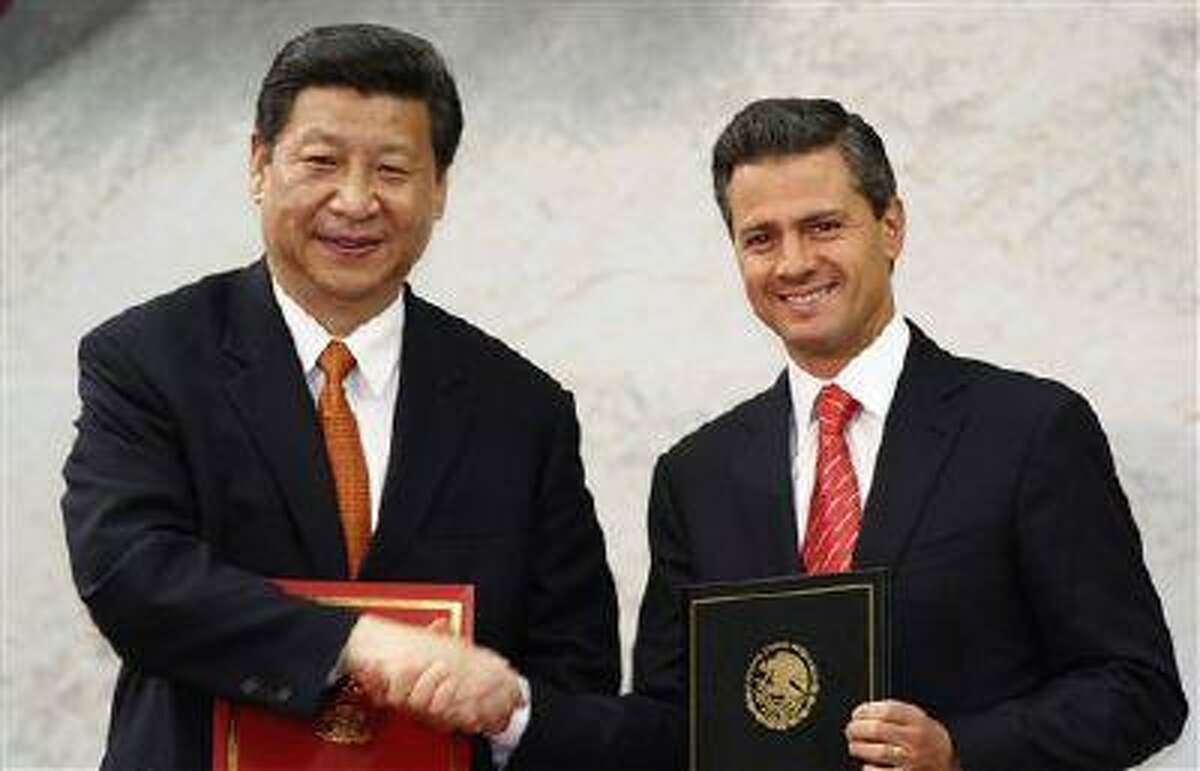In this Tuesday, June 4, 2013 file photo, Chinese President Xi Jinping, left, and his Mexican counterpart Enrique Pena Nieto pose for photographers during an agreement signing ceremony at Los Pinos presidential residence in Mexico City.(Marco Ugarte/AP)