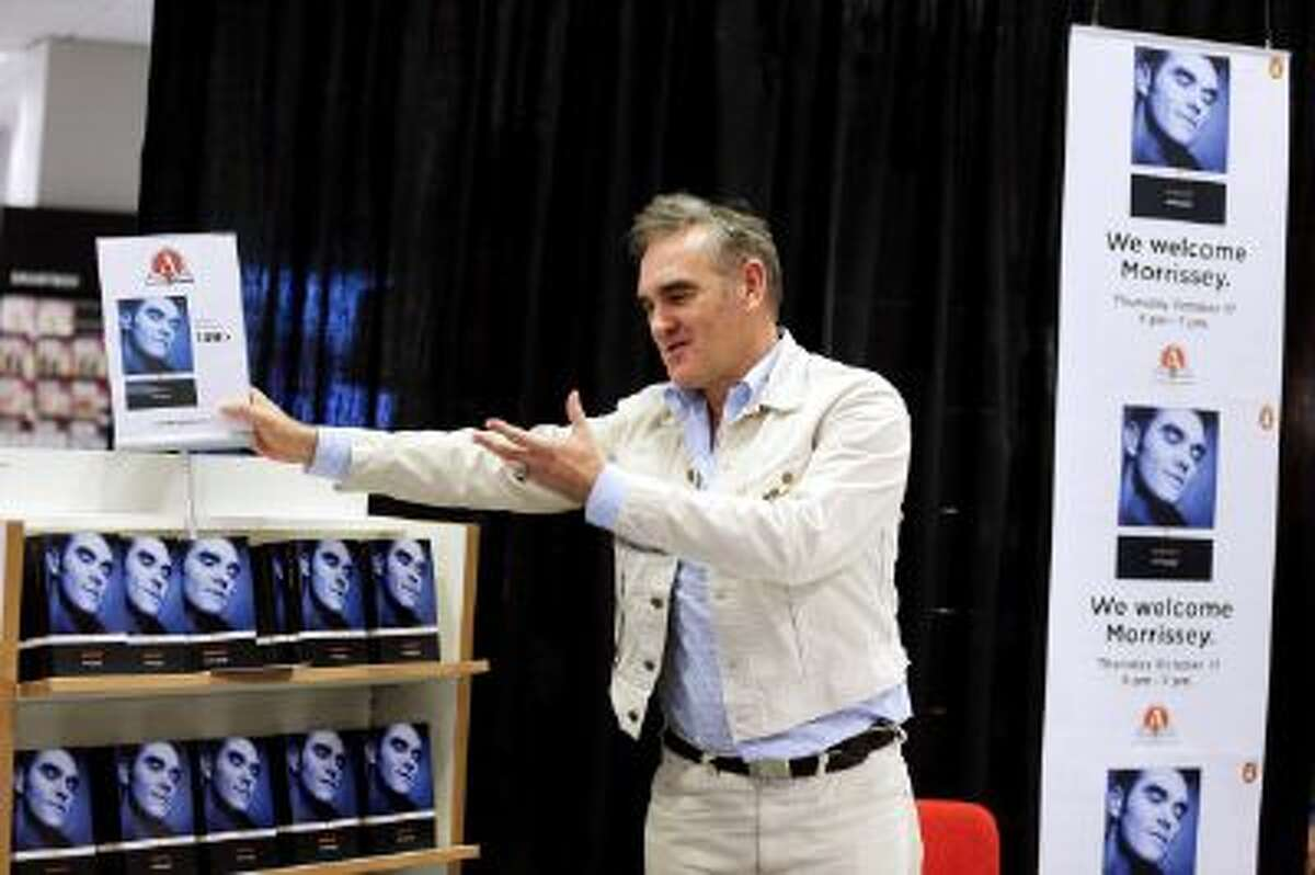 Morrissey shows his autobiography during a presentation in Goteborg, Sweden on Oct. 17, 2013.