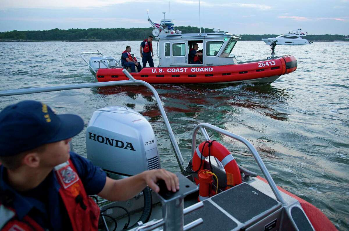 In this photo taken July 12, 2014, Seaman Robert Von Bargen, left, and other personnel on U.S. Coast Guard response boats out of Station Kings Point, N.Y., patrol near Glen Island in western Long Island sound near New Rochelle, N.Y. as they work to keep boaters at a safe distance from barge that would soon be the water base of a fireworks display. A wedding celebrated on Glen Island featured fireworks, and the Coast Guard engaged in keeping a safe zone for boaters around the pyrotechnics.