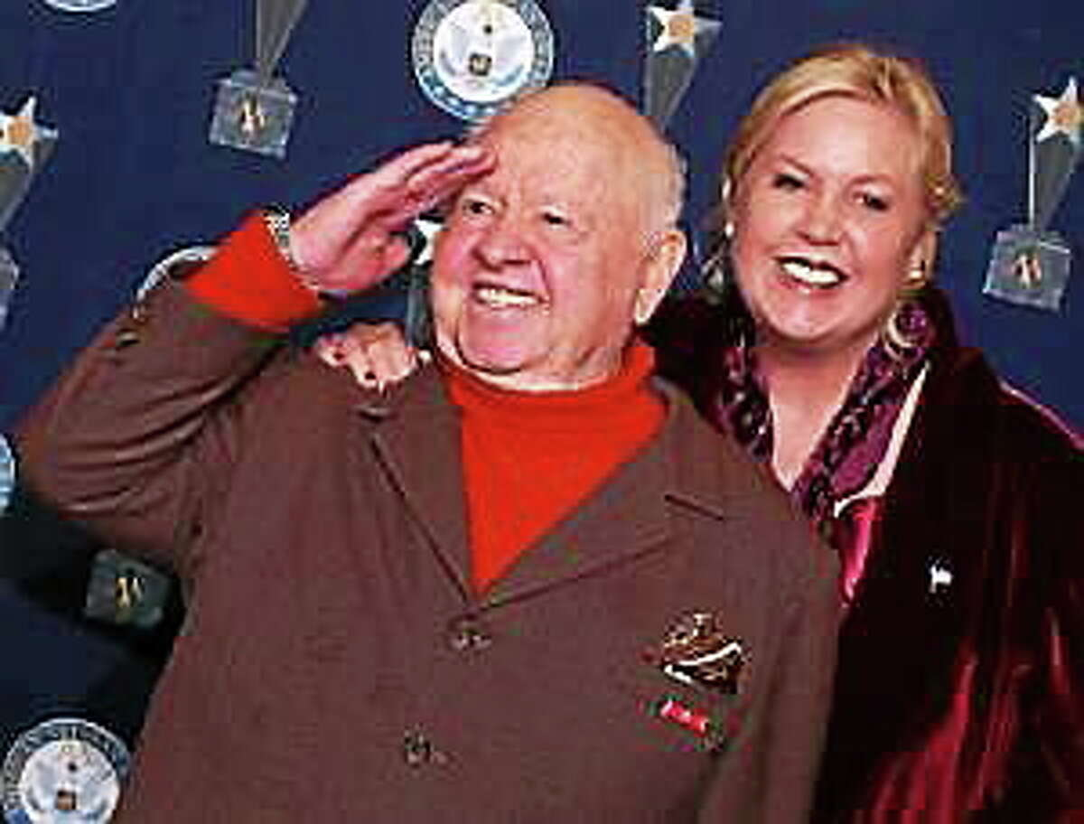 Mickey Rooney salutes the media backstage as his wife Jan, right, looks on, at the 7th Annual American Veteran Awards in Beverly Hills, Calif., in this Friday, Nov. 30, 2001 file photo.