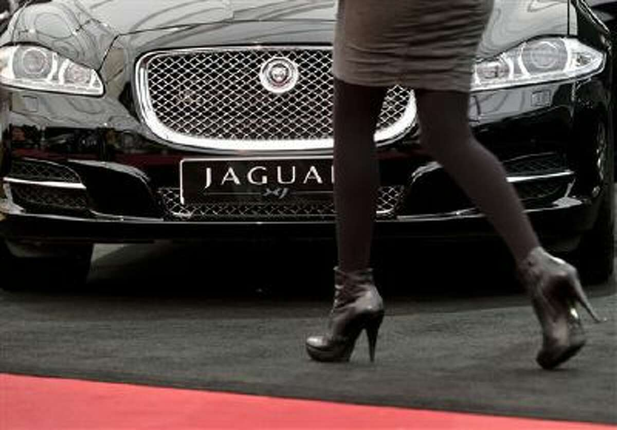 In this Wednesday, April 3, 2013, file photo, a woman passes by a Jaguar XJ during an Auto Moto Show in Bucharest, Romania.