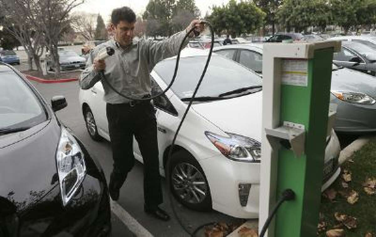 Rabih Sabbagh prepares to move his Prius as Satyen Kansara, right, goes to move his car into the Sabbagh's charging station at Infoblox in Santa Clara, Calif. on Monday, Jan. 6, 2014.