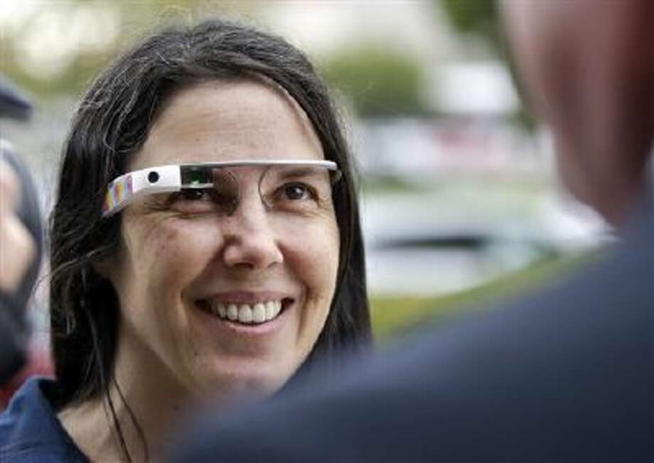 "Cecilia Abadie wears her Google Glass as she talks with her attorney Dec. 3 outside of traffic court in San Diego. The California woman believed to be the first cited for wearing Google's computer-in-an-eyeglass while driving. Google's reach into society includes many avenues, including its home-page drawings, or ""doodles."" Photo: ASSOCIATED PRESS / A2013"