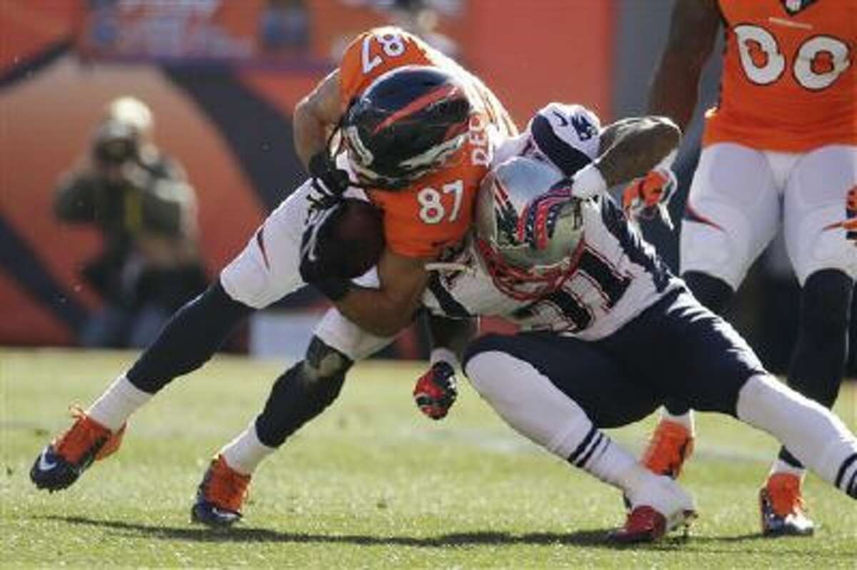 Denver Broncos wide receiver Eric Decker (87) is stopped New England Patriots cornerback Aqib Talib (31) during the first half of the AFC Championship NFL playoff football game in Denver, Sunday, Jan. 19, 2014.