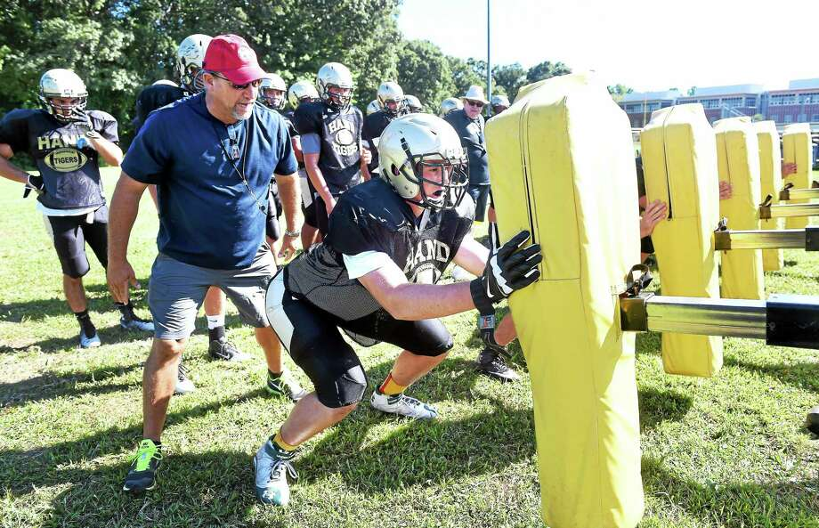 (Arnold Gold-New Haven Register)  Daniel Hand High School head football coach Steve Filippone (left) watches offensive lineman Jack Driscoll (center) hit the sled during practice on 8/29/2014. Photo: Journal Register Co.