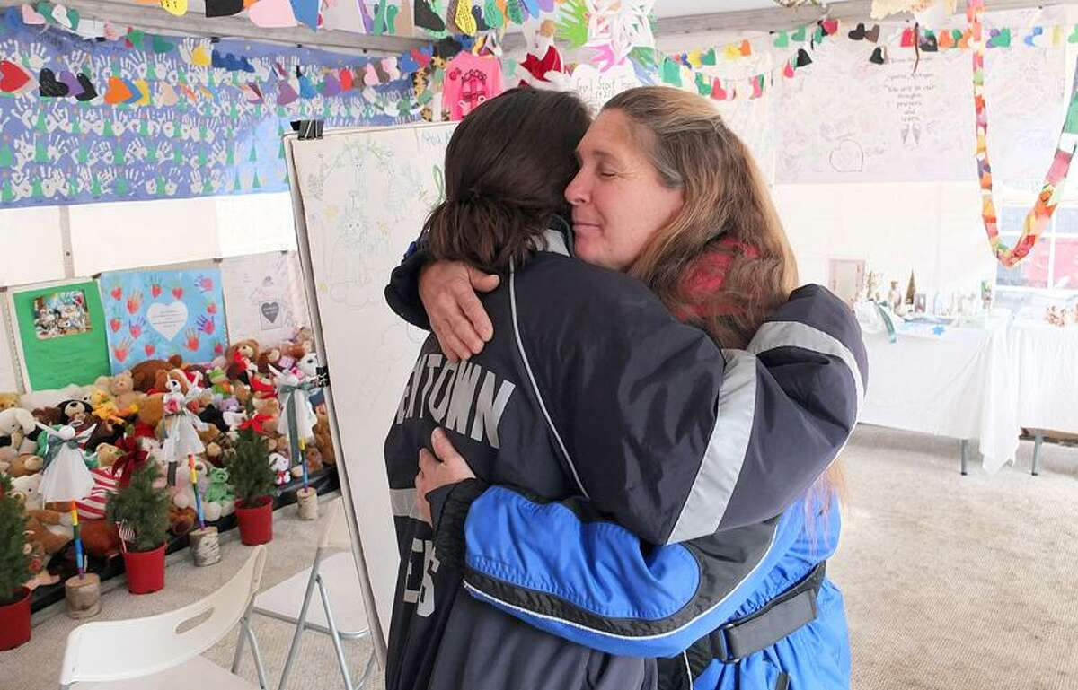 Newtown-- Chaplain Renee Gilbert (right) of Calvary Chapel of Southbury, hugs Sarah Miles, a Newtown Ambulance EMS worker as she visited the tent. The tent, on Church Hill Road, is the last remaining memorial for the victims of the Sandy Hook School shootings. Photo-Peter Casolino 2/6/13