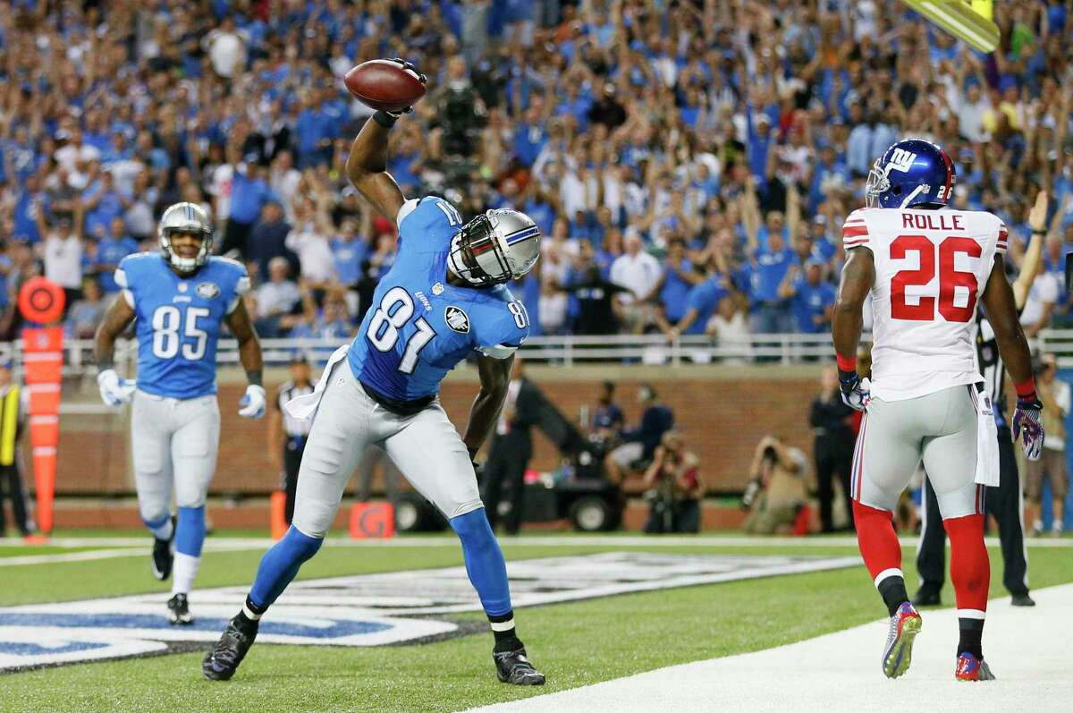 Lions wide receiver Calvin Johnson spikes the football after scoring on a 16-yard reception during the first quarter against the New York Giants in Detroit.
