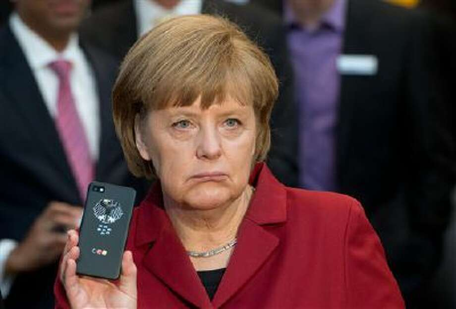 German Chancellor Angela Merkel shows off a tap-proof mobile phone during the opening round tour of the world's largest computer expo CeBIT in Hannover, Germany on March 5, 2013. Photo: AP / dpa